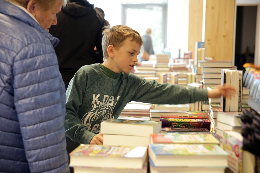 Kinderen met hun ouders op de schoolboekenbeurs